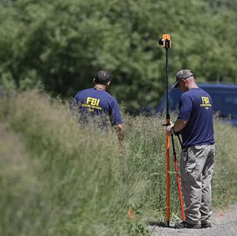 Members of the FBI Evidence Response Team survey an area in Oakland Township, Michigan (AP/Carlos Osorio)