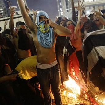 Protestors burn a Sao Paulo state flag in front of City Hall, in Sao Paulo, Brazil (AP/Nelson Antoine)