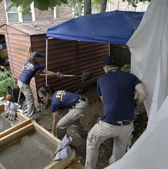 FBI agents search the garden of a New York city house once occupied by the late gangster James Burke (AP/Kathy Willens)