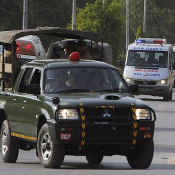 A Pakistan army vehicle leads the way for ambulances carrying caskets of foreign tourists who were killed by Islamic militants (AP)