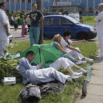 Hospital employees bide their time as experts checking the Brodno District Hospital for explosives in Warsaw (AP Photo/Czarek Sokolowski)