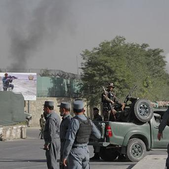 Afghan soldiers stand guard as smoke rises from the gate of the presidential palace in Kabul (AP)