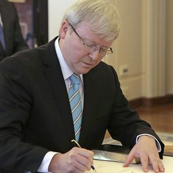 Kevin Rudd signs his commission within half an hour of Parliament resuming for what is likely to be its last day before elections (AP)