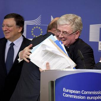 European Commission President Jose Manuel Barroso, left, European Parliament President Martin Schultz, centre, and Irish Foreign Minister Eamon Gilmore congratulate each other after the budget deal was announced (AP)