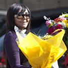 Granddaughter Ndileka Mandela carries a bunch of flowers left by wellwishers into the Mediclinic Heart Hospital (AP)