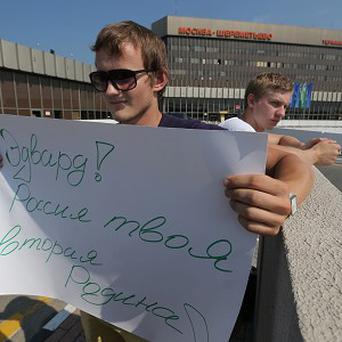 A supporter of Edward Snowden holds a poster outside Sheremetyevo airport (AP)