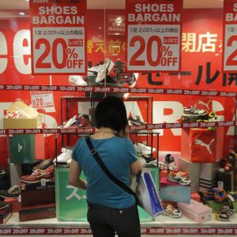 A shopper looks at a window display of a shoe shop at a department store in Tokyo (AP)