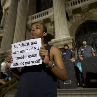 A man holds a message that reads in Portuguese;