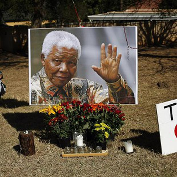 A young boy rests by a large picture of Nelson Mandela placed by the Union Building in Pretoria (AP)