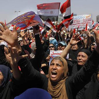 Egyptian protesters chant slogans and hold anti-Egypt's Islamist President Mohammed Morsi posters during a rally in Tahrir Square (AP)