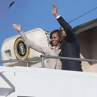 President Barack Obama and first lady Michelle Obama wave as they depart Waterkloof Air Base for a flight to Cape Town (AP)