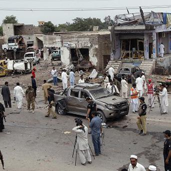 Pakistani security officials gather at the site of car bombing on the outskirts of Peshawar (AP)