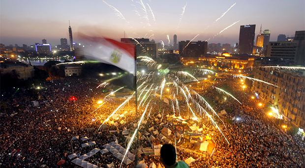 An Egyptian protester waves a national flag as Egyptians gather in Tahrir Square during a demonstration against President Mohammed Morsi
