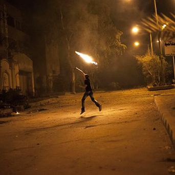 An Egyptian protester attacks the Muslim Brotherhood headquarters (AP)