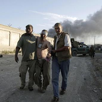 Afghan men assist an injured man after a suicide bombing at the gate to a Nato compound in Kabul (AP/Rahmat Gul)