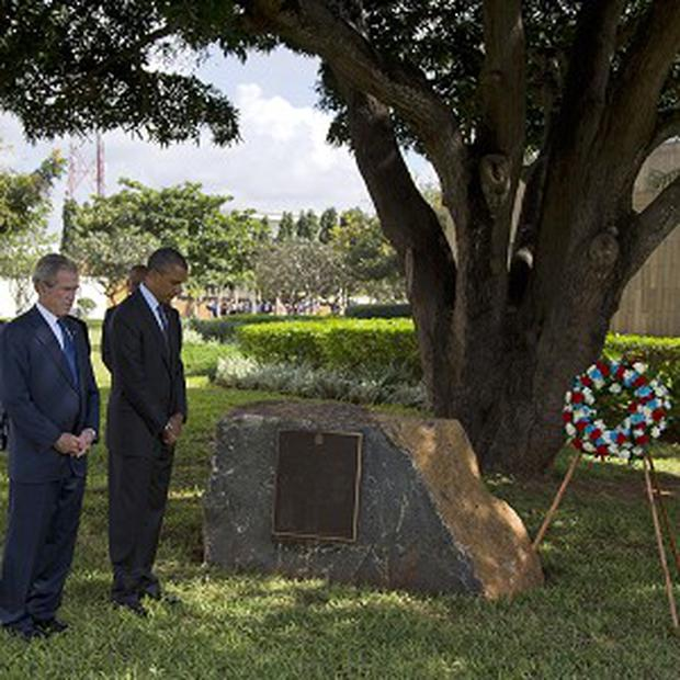 US president Barack Obama and former president George W Bush during a wreath-laying ceremony in Dar es Salaam, Tanzania (AP)