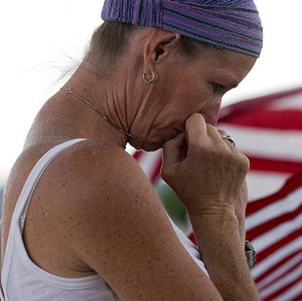 Wendy Tollefsen lays flowers at a makeshift memorial outside a fire station in Prescott, Arizona (AP/Julie Jacobson)