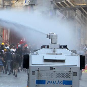 Police use a water cannon against protesters in Istiklal Street, Istanbul's main shopping strip during clashes (AP)