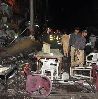 Police officers examine the site of a bomb blast at a food street in Lahore, Pakistan (AP/KM Chaudary)