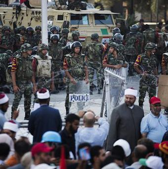 Egyptian soldiers stand guard at the gates of the Republican Guard's building during a protest by Morsi supporters (AP)