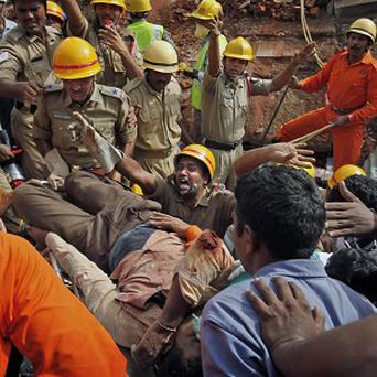 Fire officials clear the way after rescuing an injured man from a collapsed building in India (AP)