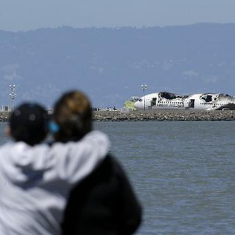 People look towards the wreckage of the plane that crashed upon landing at San Francisco International Airport (AP)
