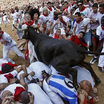 A bull jumps over revellers lying on the bull ring at the end of the fifth run of the San Fermin festival (AP)