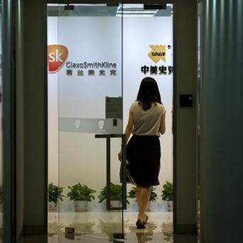 A woman enters an office of GlaxoSimthKline in Beijing. China's police ministry has accused executives of conducting a large and long-running bribery campaign (AP)