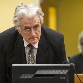 Former Bosnian Serb leader Radovan Karadzic takes a seat after arriving at the courtroom (AP)