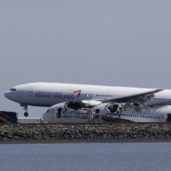 An Asiana plane lands behind the wreckage of Asiana Flight 214, which crashed on Saturday at San Francisco International Airport (AP)
