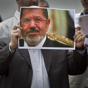 A man holds a poster of Egypt's ousted President Mohammed Morsi (AP)