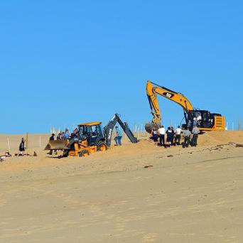 Firefighters and police dig through a sand dune while searching for a missing boy (AP/The News Dispatch, Julie McClure)