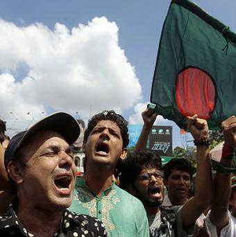 Bangladeshi activists shout slogans as they protest after a 91-year-old former chief of the Islamic party was sentenced to 90 years in jail (AP)