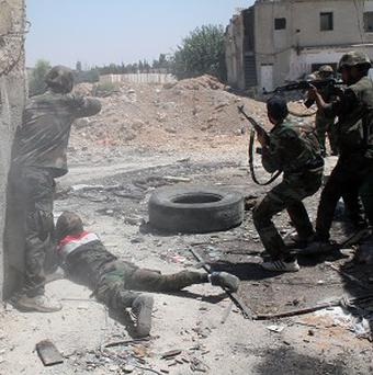 Syrian army personnel target rebel fighters in the Damascus suburb of Jobar (AP)