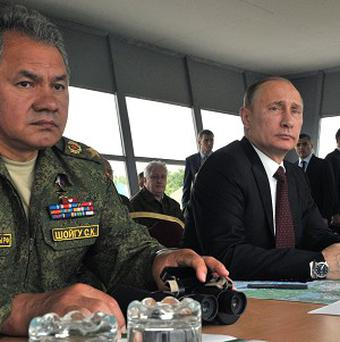 Russian president Vladimir Putin, right, watches military exercises on Sakhalin Island (AP)
