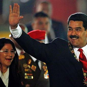 Venezuela's president Nicolas Maduro waves as first lady Cilia Flores looks on (AP/Fernando Llano)