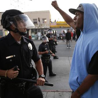 A protester confronts a Los Angles police officer during a demonstration over the acquittal of George Zimmerman (AP)