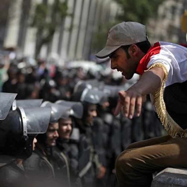 A supporter of Egypt's ousted president Mohammed Morsi talks to riot police near Tahrir Square in Cairo (AP)