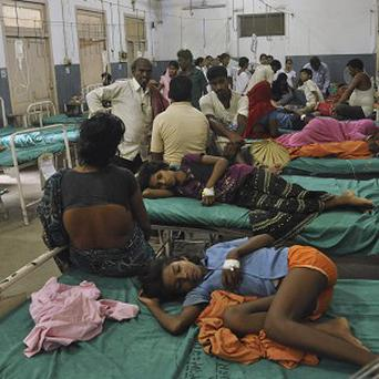 Indian children who fell ill after eating a free school lunch lie at a hospital in Patna (AP)