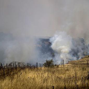 Smoke rises following explosions of mortar shells from Syria on the Israeli-controlled Golan Heights (AP)