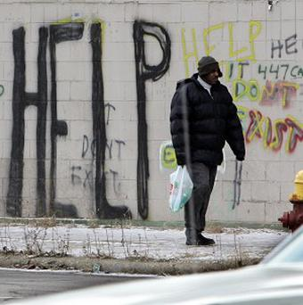 A man walks by graffiti in downtown Detroit, which has filed for bankruptcy (AP/Carlos Osorio)
