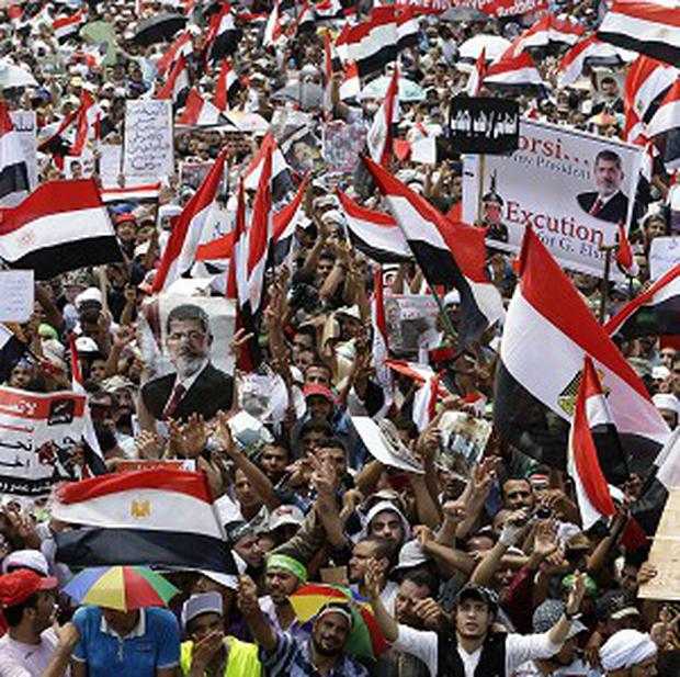 Supporters of Egypt's ousted president Mohammed Morsi wave flags during a demonstration (AP)