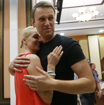 Russian opposition leader Alexei Navalny embraces his wife Yulia in a courtroom in Kirov, Russia