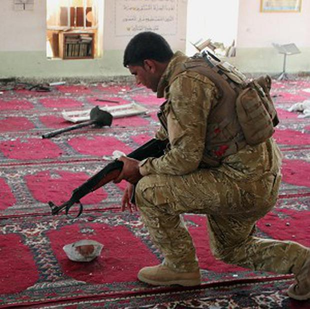 An Iraqi army soldier inspects the damage after a blast inside the Abu Bakir al-Sideeq mosque (AP)