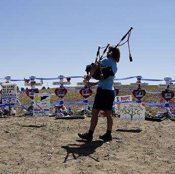 Becky Nelson plays the bagpipes at a temporary memorial for the victims of the cinema shooting in Aurora, Colorado (AP)