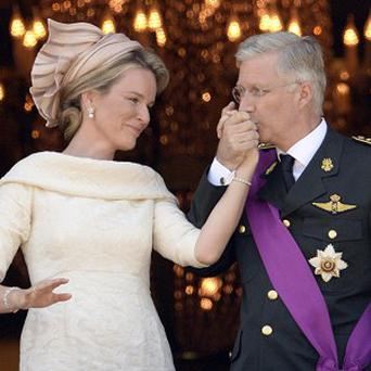 Belgium's King Philippe kisses the hand of Queen Mathilde as they stand on the balcony of the royal palace in Brussels (AP)