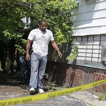 An East Cleveland police officer searches a house where one of three bodies were recently found (AP)