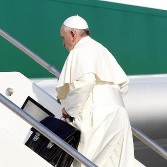 The pope carries his own luggage onto the flight (AP)