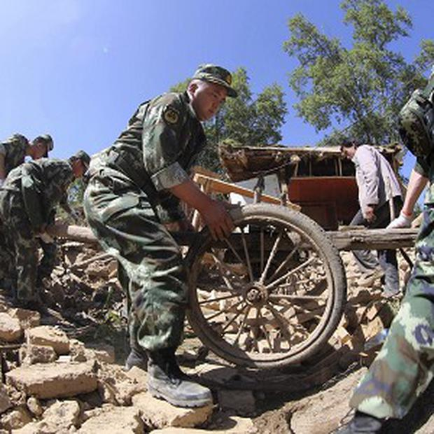 Police help residents remove belongings from quake-damaged houses in Lalu village of Hetuo township in Minxian in north-west China (AP)