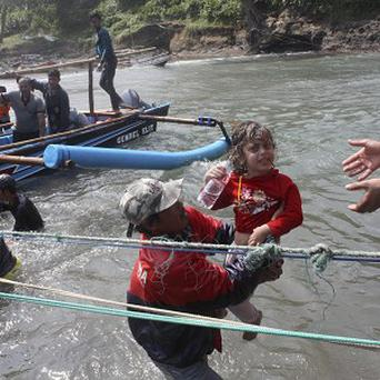 A rescuer carries a child to safety after a boat carrying asylum seekers sank off Java island in Cianjur, Indonesia (AP)